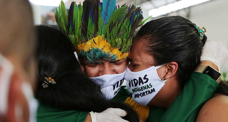 Tre personer med munskydd kramar varandra. De är på en begravning. De tillhör urfolk i Amazonas regnskog. En person har fjädrar på huvudet.
