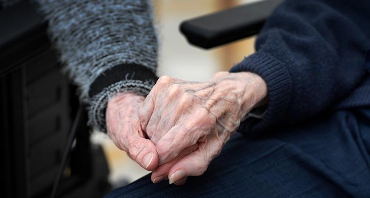 Två personer håller varandra i händerna.
