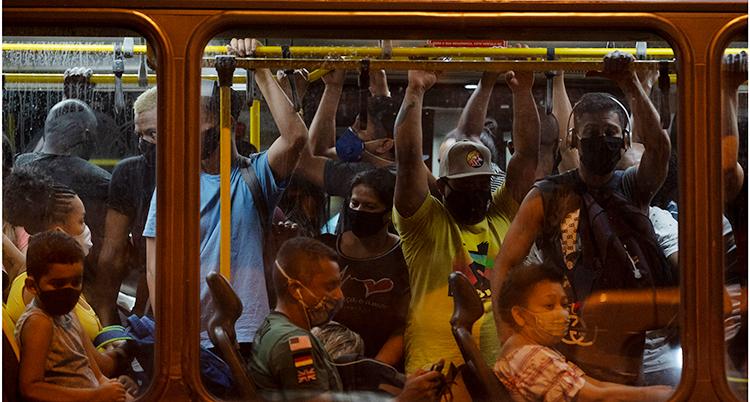 Människor trängs på en buss i Brasilien. Många har på sig munskydd.
