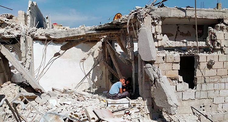 Små pojkar sitter i ruinerna av ett hus som har blivit förstört i kriget i Syrien.