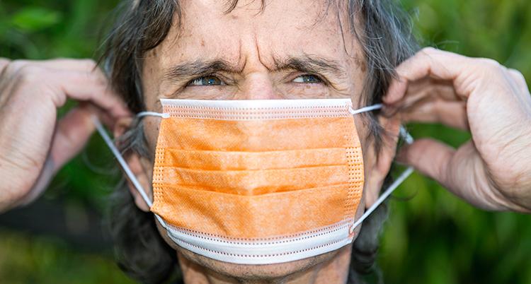En man tar på sig ett orange munskydd.