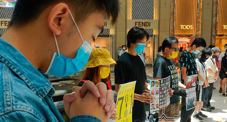 Människor i Hongkong protesterar mot Kinas nya lag. De har på sig munskydd och håller i skyltar.