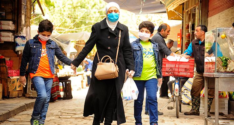 En kvinna och två barn på en marknad i Syrien. Kvinnan håller barnen i händerna och de har på sig munskydd.