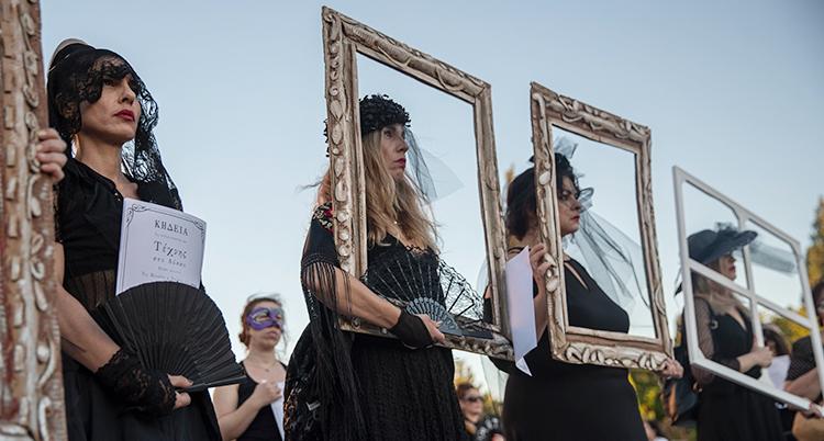 Kvinnorna är klädda i svart. De håller upp ramar.