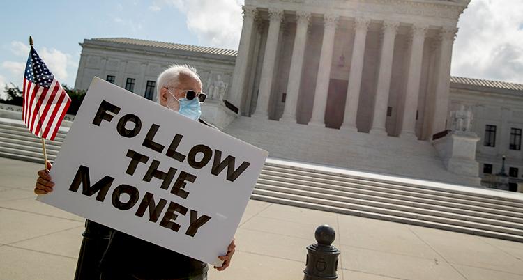 """En man håller upp en vit skylt med svart text. På skylten står det """"Follow the money"""". På svenska: Följ pengarna."""
