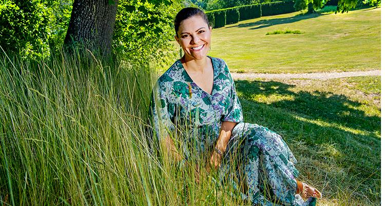 Kronprinsessan Victoria sitter i gräset. Hon ler och har en grönblå sommardräkt på sig.