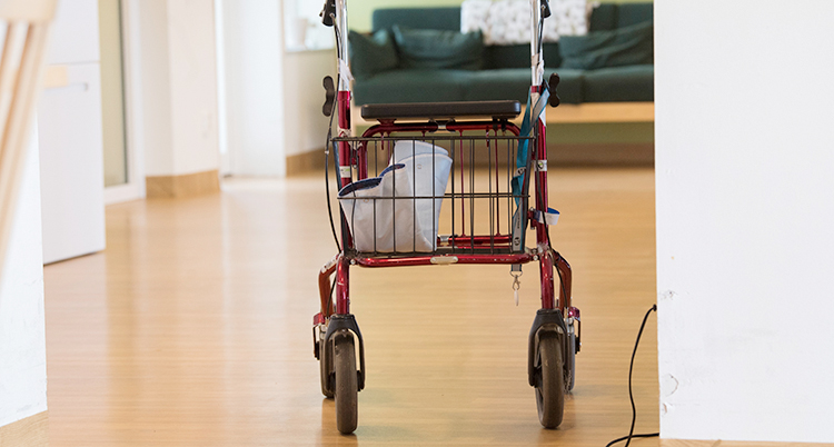 En rullator står på ett golv i ett äldreboende.