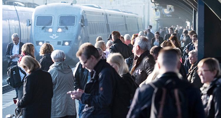 Många människor står och väntar på ett tåg. Tåget står på perrongen.