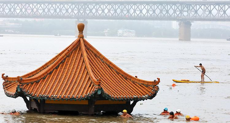 Människor simmar förbi en översvämmad byggnad i Yangtzefloden i Kina.