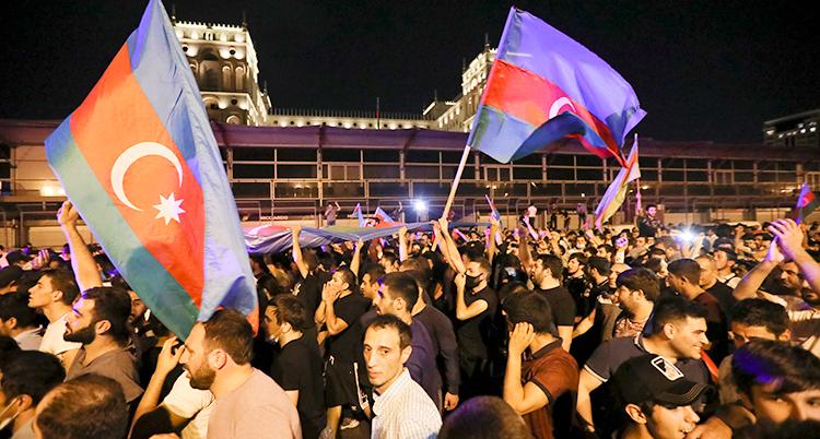 Många demonstrerar i Azerbajdzjan. Två personer håller upp landets flagga.