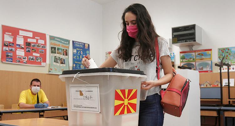 En mörkhårig ung kvinna med rött munskydd röstar i valet. Hon lägger en röstsedel i en låda.