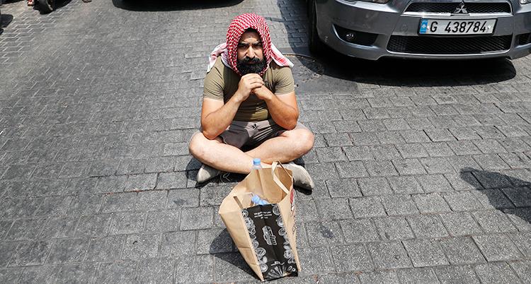 En man sitter ner på gatan med benen i kors. Han har shorts på sig och ett slags turban på huvudet.