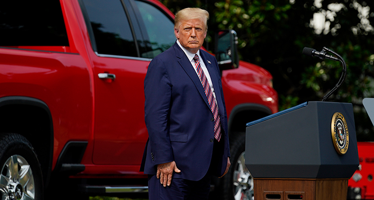 Donald Trump har blå kostym och står framför en röd bil.
