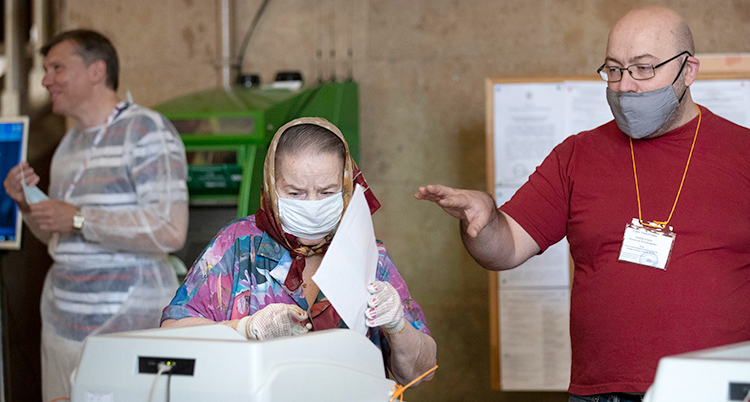 En äldre kvinna med munskydd röstar i valet i Ryssland.