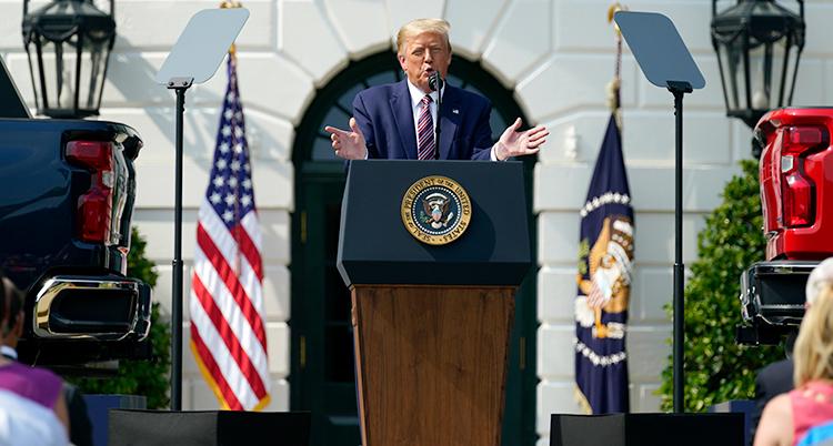 Donald Trump pratar på ett event. Han gestikulerar med armarna och har på sig blå kostym.