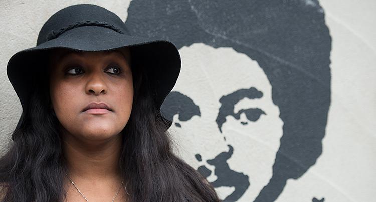 Betlehem Isaak har en svart hatt på sig. Hon står vid en vägg. På väggen är det en bild på hennes pappa, Dawit Isaak.