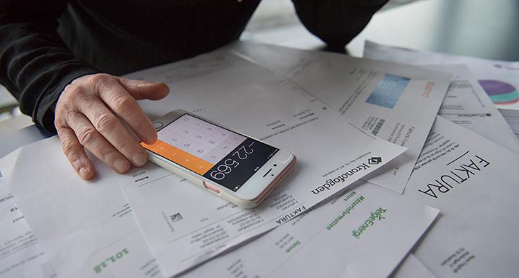 Bilden visar en person som sitter och räknar på en miniräknare. På bordet finns det massor av räkningar.