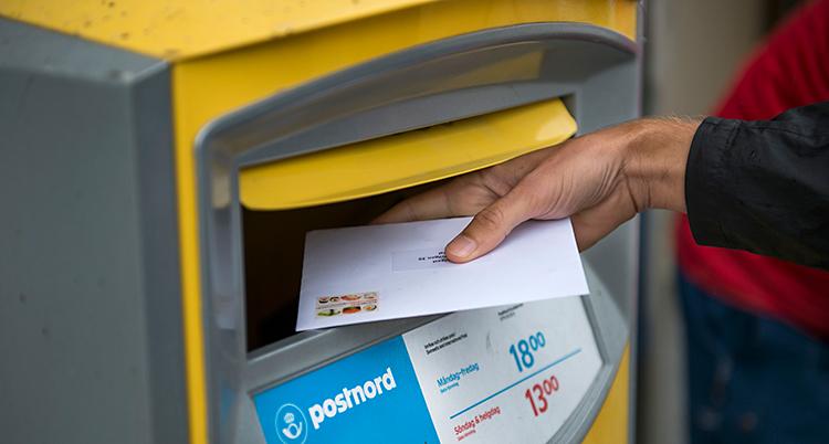 En person lägger ett brev i en gul postlåda.