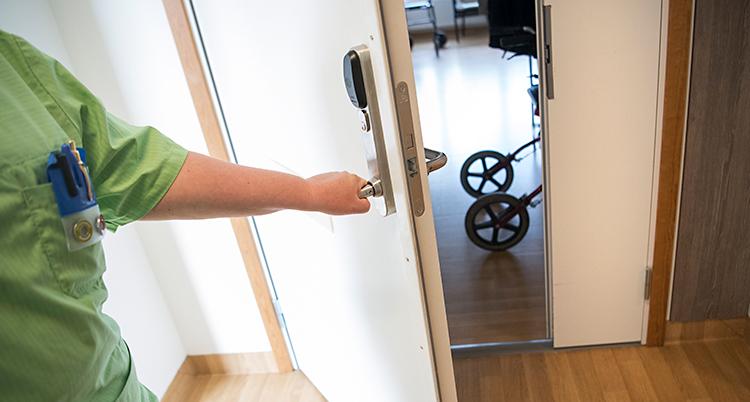 Bilden är tagen på ett hem för gamla. En sköterska öppnar dörren till en lägenhet. I lägenheten syns en rullator.