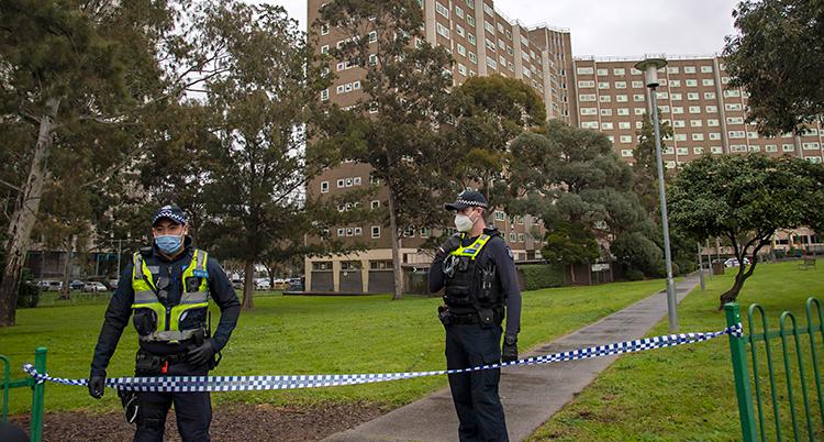 Två poliser står utomhus. De har satt upp band som spärrar av. I bakgrunden står ett stort hus med lägenheter.