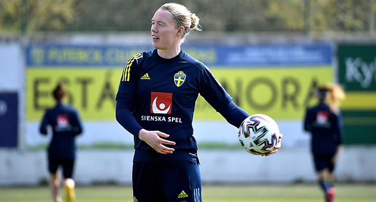 Hon står på en fotbollsplan. Hon har träningskläder. Hon har en boll i handen som hon är på väg att kasta.