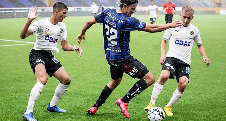 Bilden är från en match i fotboll. Två spelare i vita tröjor försöker ta bollen från en spelare med blå och svart tröja.