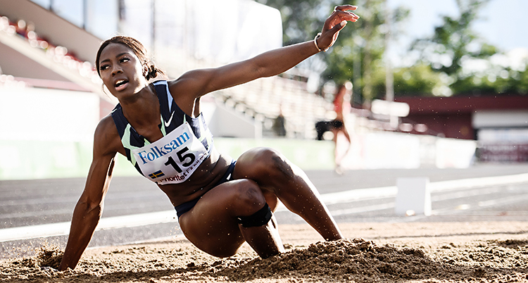 Hon har precis gjort ett hopp i längdhopp. Bilden är tagen när hon landar i en grop med sand. Hon har en nummerlapp på bröstet.