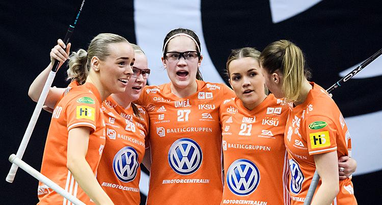 Bilden är från en match i innebandy. Några kvinnor kramas efter ett mål. De har orange tröjor och innebandyklubbar i händerna.