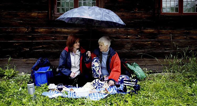 Två personer sitter mot en husvägg. De sitter på en filt. De har picknick. En av dem håller i ett paraply.