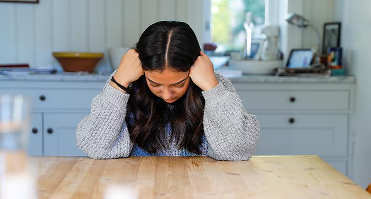 En kvinna sitter vid ett bord. Hon har armbågarna på bordet. Hon vilar huvudet i händerna. Hon ser ut att må dåligt.