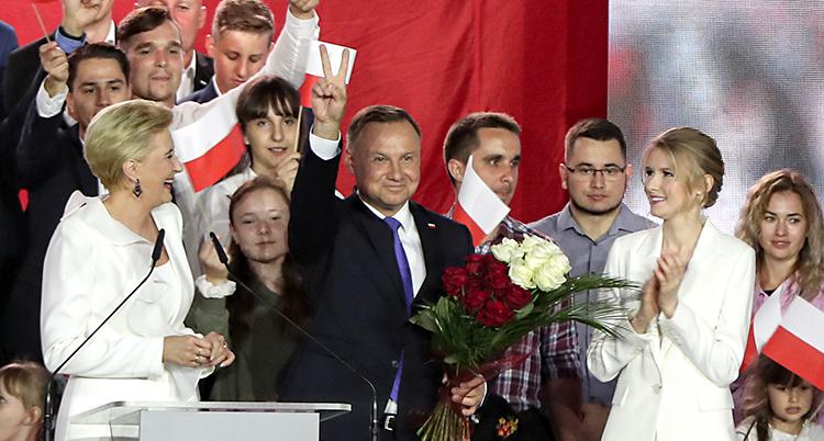 Han står på en scen. Han är glad och gör ett v-tecken med fingrarna. Många människor står runt honom.