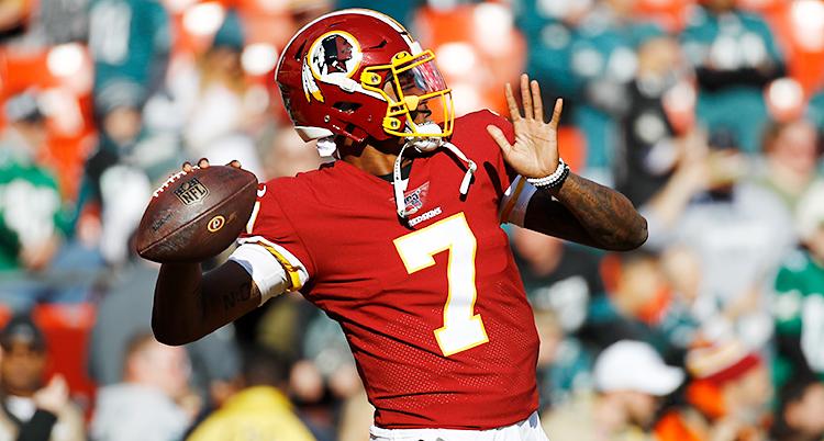 Bilden är från en match i amerikansk fotboll. En spelare har bollen i handen och ska kasta den. Han har en röd tröja på sig och en röd hjälm.