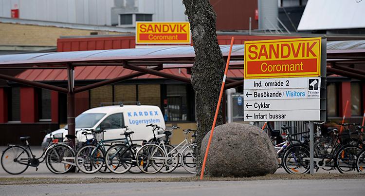 Bilden är tagen på gatan utanför företaget Sandvik. Vi ser en skylt där det står Sandvik. Vi ser också en vit bil som står framför företagets stora byggnad.
