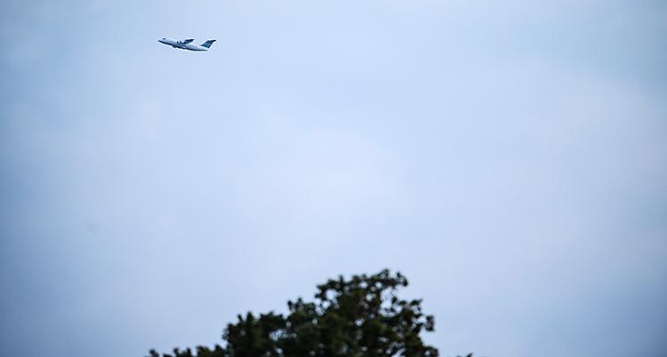 Vi ser ett flygplan uppe i luften. I nedre delen av bilden syns toppen av träd.