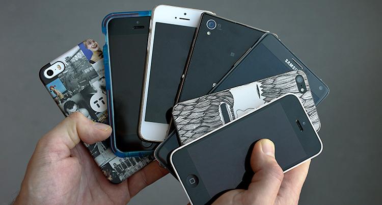 Bilden visar två händer. Händerna håller upp flera smarta mobiltelefoner.