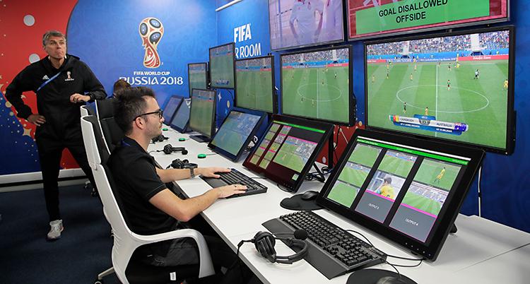 En man sitter i ett rum. Han har många skärmar framför sig. Det är en fotbollsmatch på skärmarna.