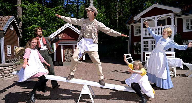 Barnskådespelare framför några röda stugor gungar på en gungbräda.