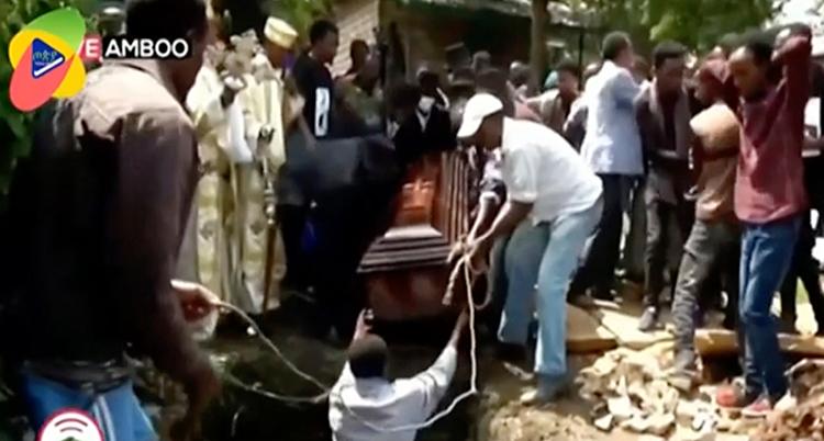 Flera personer står runt en grav. Några personer lyfter ner en kista i graven.