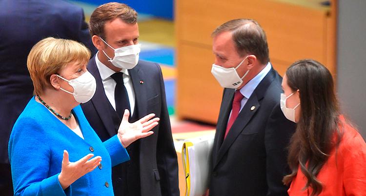 Fyra personer står och pratar. Alla har munskydd på sig.