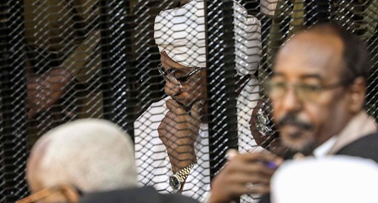 Omar al-Bashir med handen lutad mot huvudet bakom ett galler.