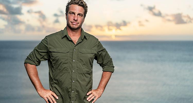 Han tittar in i kameran. Han står vid havet. Han en grön skjorta på sig som är uppkavlad i ärmarna, och han har händerna i sidorna.