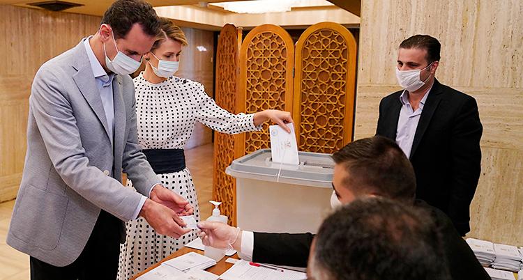En man och en kvinna står vid ett bord. Där finns olika lappar för att rösta. Runt bordet finns folk som jobbar med valet. Alla personer har munskydd på sig.