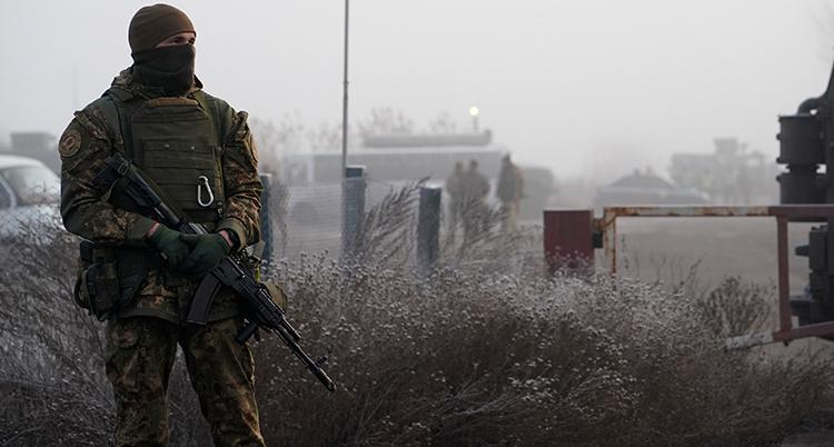En man i militärkläder och svart mask för ansiktet står och håller i ett vapen.