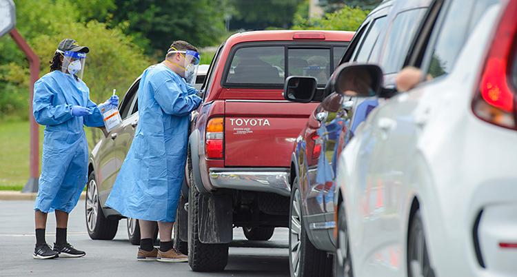 Det är en kö med bilar. Vid en bil står två personer. De har skyddskläder och mask för ansiktet.