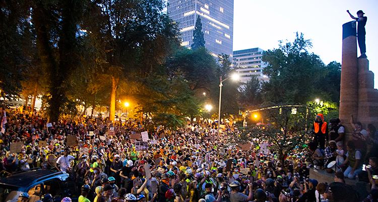 En massa människor har samlats utomhus i en stad.