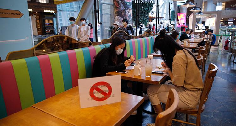 Två personer med munskydd sitter vid ett cafébord i Hongkong. Bordet bredvid har en skylt med förbud att sätta sig.