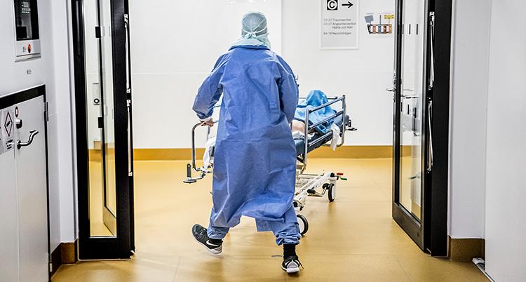 En skyddsklädd person drar en sjuksäng på ett sjukhus.