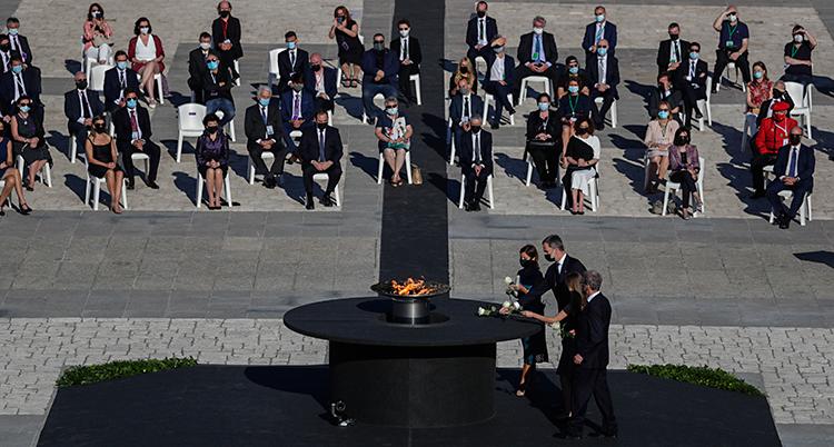 Bilden är tagen på ett torg. På torget finns en eld som brinner. Människor lägger blommor runt elden. Bredvid elden sitter människor på stolar.