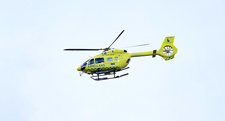 Vi ser en gul helikopter i luften. Det står Ambulans på helikoptern.