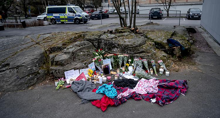 Bilden är tagen utomhus. På marken finns det ljus och blommor och filtar. I bakgrunden står en polisbil.